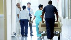 Positive multi ethnic team of hospital staff work and consult with senior couple - stock footage