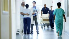 Busy multi ethnic team of hospital nurse work and consult with senior couple Stock Footage