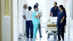 Staff of hospital work on corridor and male doctor consult with senior couple - stock footage