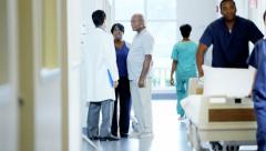 Multi ethnic team of hospital staff work and consult with senior patient - stock footage