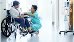 African American female staff and disabled patient consult in medical centre - stock footage