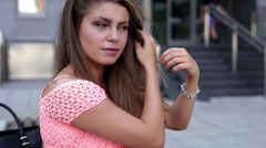 Pretty girl fixing her hair while waiting for her date. Stock Footage