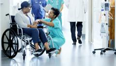 African American female staff and disabled patient consult in medical center - stock footage