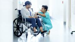 African American female staff and patient on wheelchair consult in hospital - stock footage
