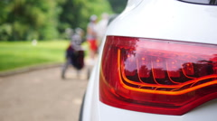 Close up of the side of a white car with golf player Stock Footage