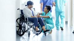 African American female doctor and patient on wheelchair consult in hospital - stock footage