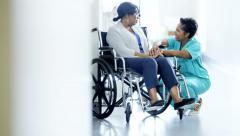 African American female nurse and patient on wheelchair in medical centre - stock footage