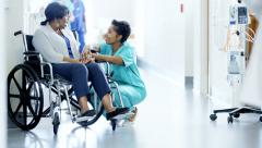 African American female nurse and disabled patient consult in medical centre Stock Footage