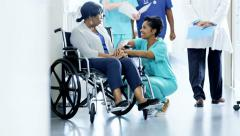 Multi ethnic team and empathy nurse and senior patient on wheelchair in hospital - stock footage