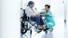 Portrait of African American female nurse and patient on wheelchair in hospital - stock footage
