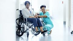 Portrait of African American female and patient on wheelchair in medical centre - stock footage
