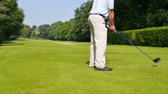 Man playing a drive on a golf course Stock Footage