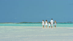 Caucasian family wearing white clothes barefoot on a beach - stock footage
