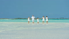 Caucasian family wearing white clothes barefoot on a beach Stock Footage