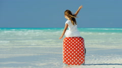 Young Caucasian girl child playing on beach with travel suitcase - stock footage