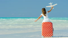 Happy Caucasian child on beach with a suitcase and model airplane Stock Footage