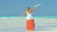 Blonde Caucasian girl sitting on suitcase with model airplane on a beach - stock footage