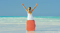 Blonde female Caucasian child on beach sitting on a suitcase Stock Footage