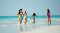 Healthy male female Caucasian family on tropical beach in swimwear - stock footage