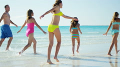 Caucasian family wearing colorful swimwear barefoot on beach - stock footage