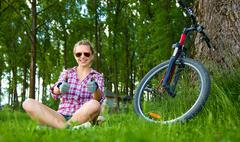Young cyclist sitting in the grass and showing thumbs up gesture - stock photo