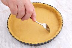 Woman using fork to prick holes in an uncooked pie crust Stock Photos