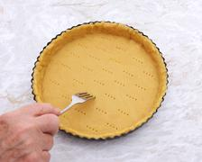 Woman finishes pricking holes in a pastry pie crust - stock photo