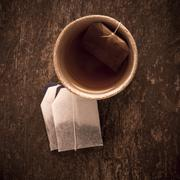 Teacup filled with hot tea and teabag on rustic wooden table - stock photo