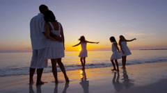 barefoot Caucasian family on a beach together at sunset - stock footage