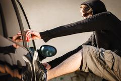 Transportation and crime- thief breaking car lock Stock Photos