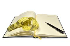 Open planner, with pen and tape measure - stock photo