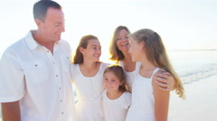 Portrait of a smiling Caucasian family wearing white clothes on beach - stock footage