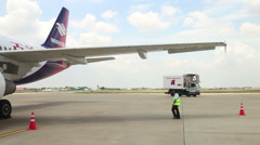 A ground service vehicle slowly approaches a plane at Cambodia's Intl airport Stock Footage