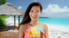 Beautiful Asian Chinese girl with party cocktail drink on beach - stock footage
