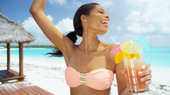Smiling young ethnic female enjoying colorful cocktail on beach Stock Footage