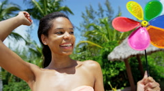Happy young ethnic girl on tropical beach with toy pinwheel - stock footage