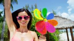 Asian Chinese girl in bikini having fun with bright toy pinwheel Stock Footage