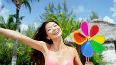 Beautiful Asian Chinese girl having beach fun with toy windmill on vacation Stock Footage