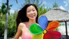 Asian Chinese Caribbean island girl playing outdoor with toy pinwheel - stock footage
