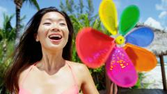 Happy ethnic Asian Chinese girl on tropical beach with toy pinwheel - stock footage