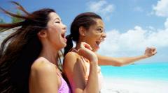 Laughing multi ethnic girls enjoying tropical beach - stock footage