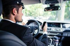 Male chauffeur riding car Stock Photos