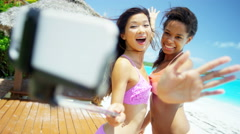 Beautiful African American Asian Chinese girls sing selfie stick on beach - stock footage