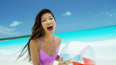 Asian Chinese girl playing with beach ball at leisure resort Stock Footage