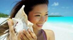 Ethnic Asian Chinese female holding conch shell on beach - stock footage