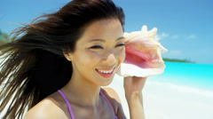 Smiling Asian Chinese girl with conch shell at vacation resort Stock Footage