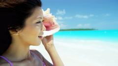 Beautiful Asian Chinese girl holding conch shell on tropical beach Stock Footage