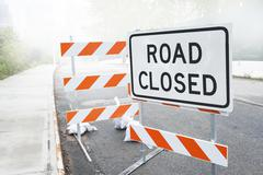 Dusty road closed sign on a city road Stock Photos
