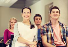 group of smiling students in lecture hall - stock photo