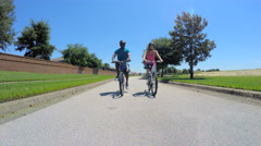 Young active African American man and woman cycling to keep fit outdoors - stock footage